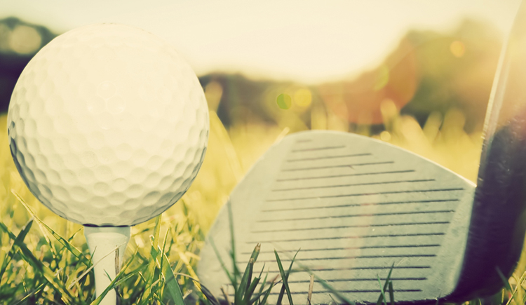 Playing golf, ball on tee and golf club about to shot. Vintage,